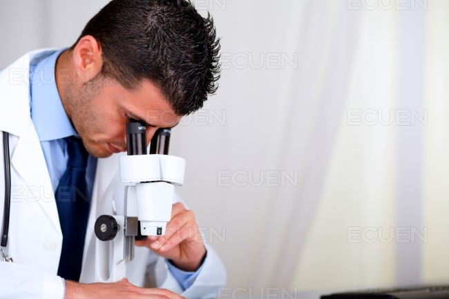 Attractive hispanic doctor using a microscope stock photo