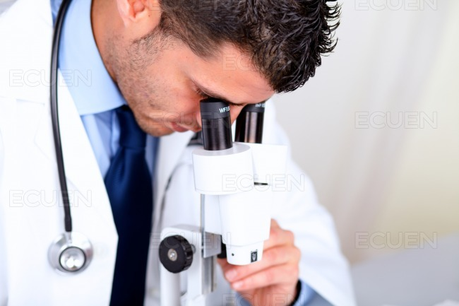 Attractive latin doctor using a microscope stock photo