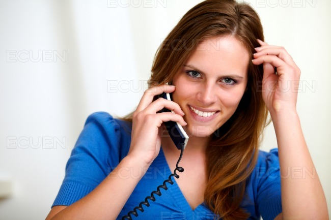 Attractive smiling blonde young woman on phone stock photo