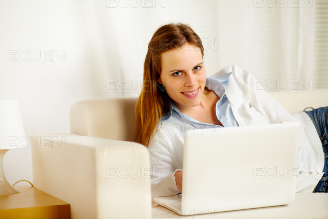 Attractive woman lying on sofa with a laptop stock photo