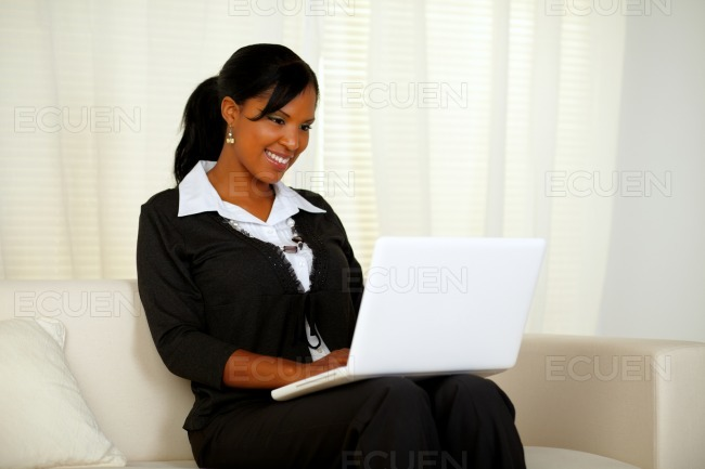 Attractive woman on black suit working on laptop stock photo
