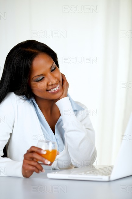 Attractive woman reading on laptop stock photo