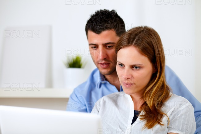 Attractive young couple using laptop together stock photo