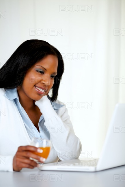 Attractive young woman reading on laptop stock photo