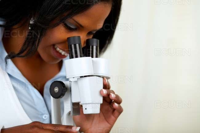 Beautiful american black woman with a microscope stock photo