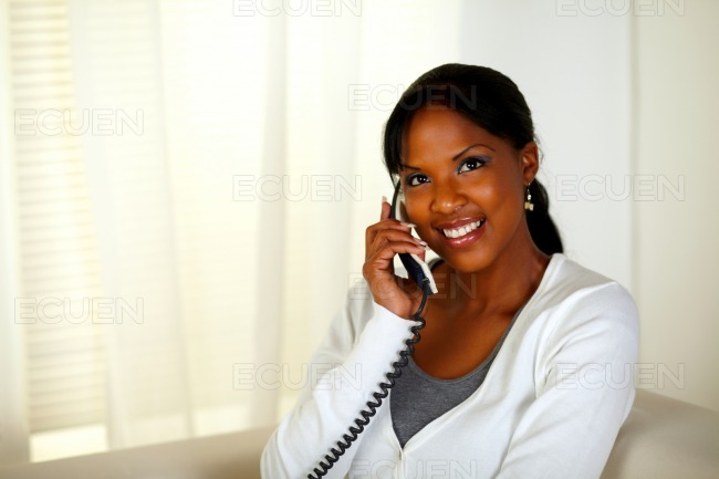 Beautiful black woman conversing on phone stock photo