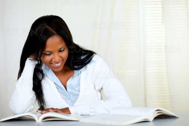 Beautiful black woman smiling and reading a book stock photo