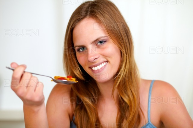 Beautiful blonde girl smiling and eating stock photo