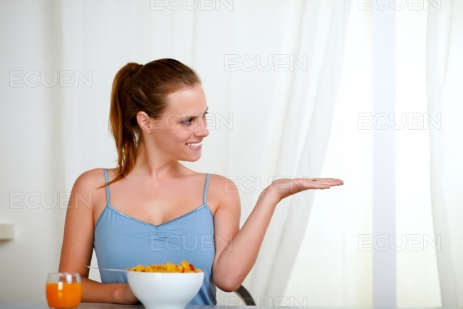 Beautiful blonde woman eating breakfast stock photo