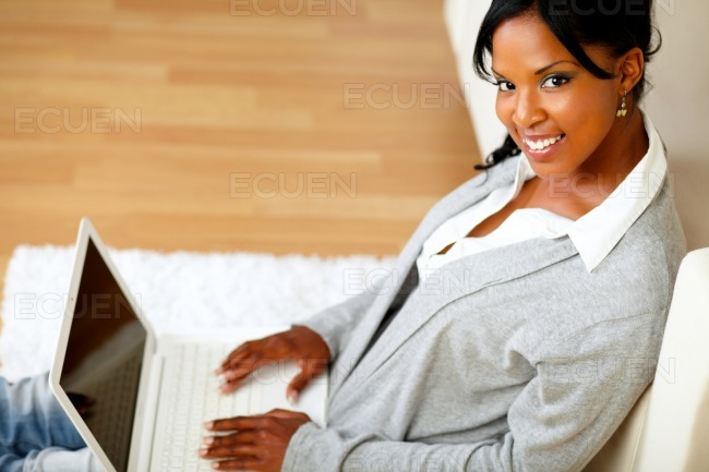Beautiful girl smiling at you with her laptop stock photo