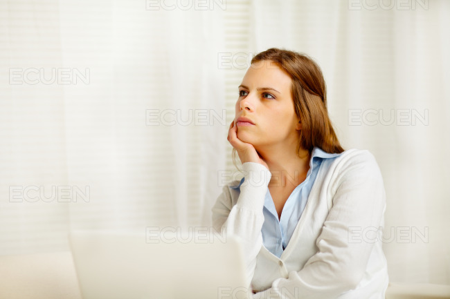 Beautiful girl thinking in from laptop stock photo