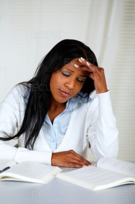 Beautiful student with headache browsing a book stock photo
