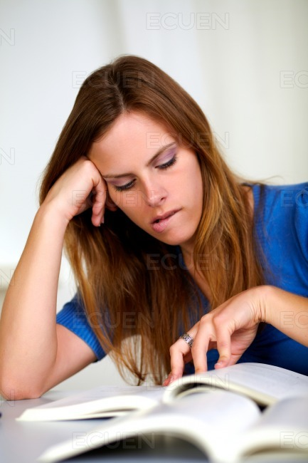 Beautiful tired blonde young girl studying stock photo
