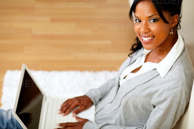 Beautiful woman smiling at you with her laptop stock photo