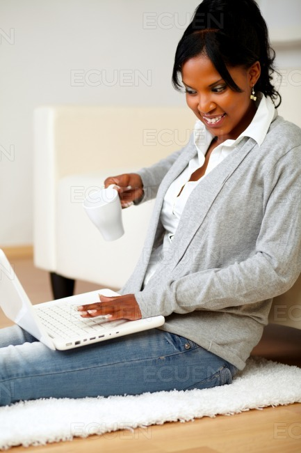 Beautiful woman with a mug in front of her laptop stock photo