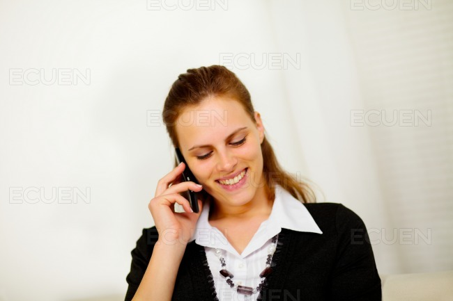 Beautiful young businesswoman on mobile phone stock photo
