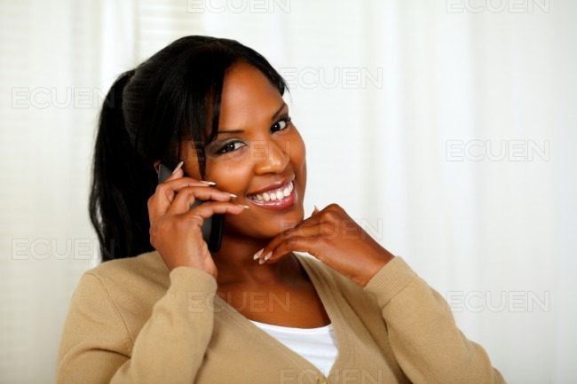 Beautiful young woman conversing on mobile phone stock photo