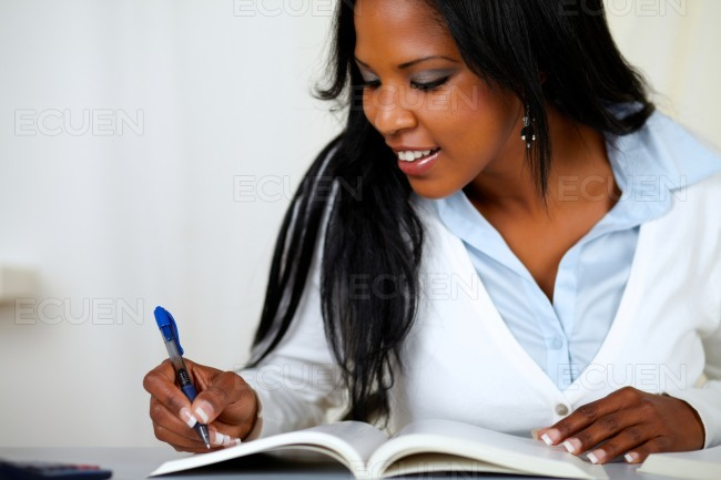 Beautiful young woman smiling and studying stock photo