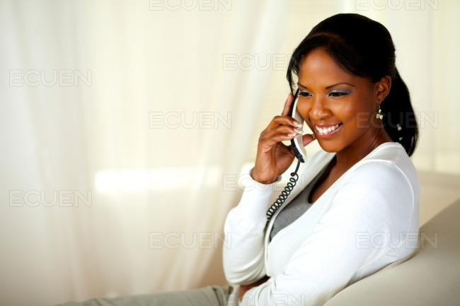 Beautiful young woman smiling on phone stock photo