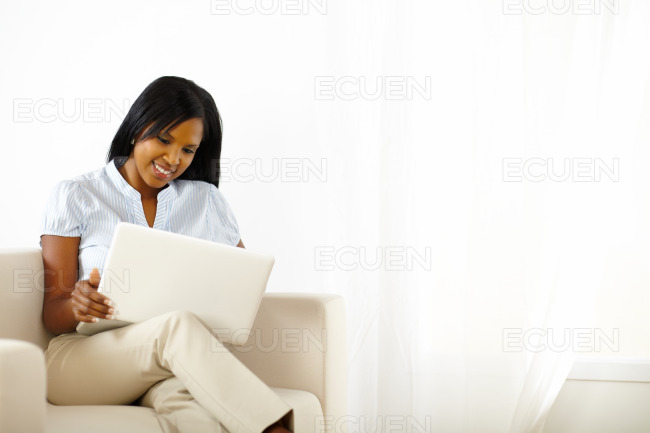 Beautiful young woman working on laptop stock photo