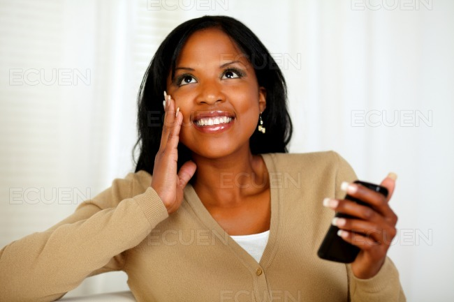 Black woman holding mobile phone and looking up stock photo