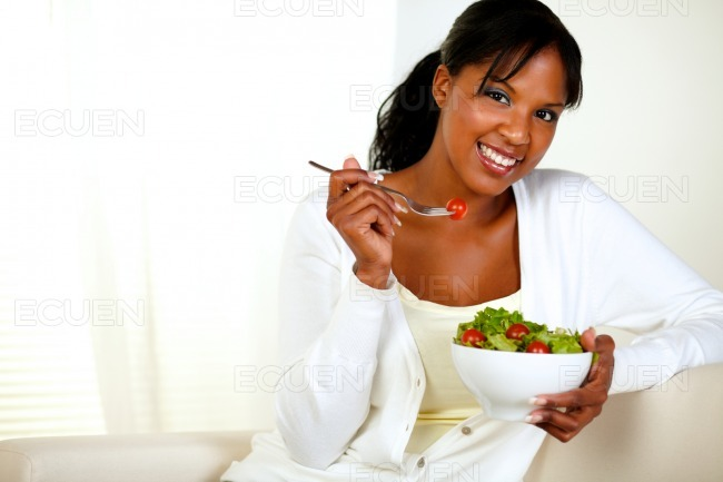 Black woman looking at you as she eats her salad