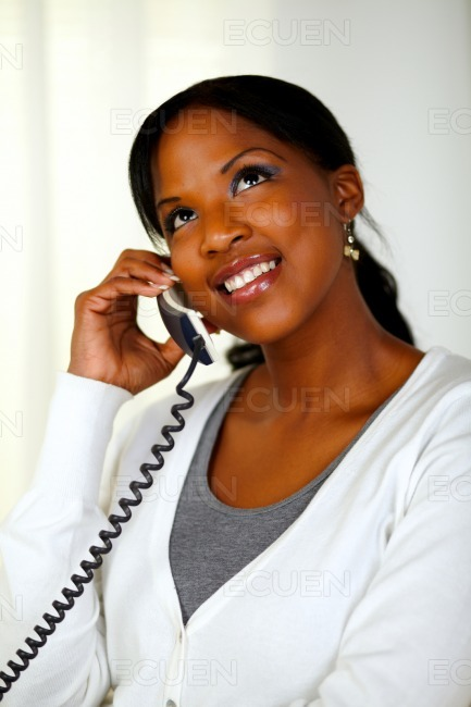 Black woman looking up while talking on phone stock photo