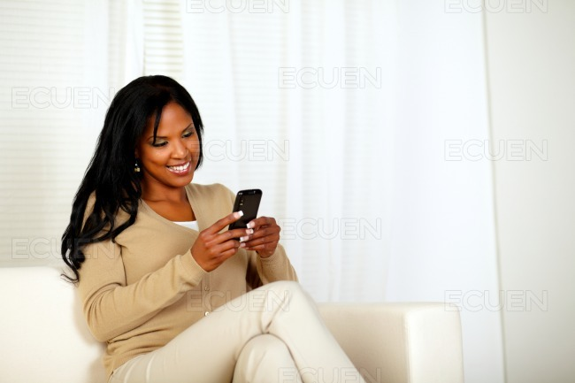 Black woman sending a message by the cellphone stock photo
