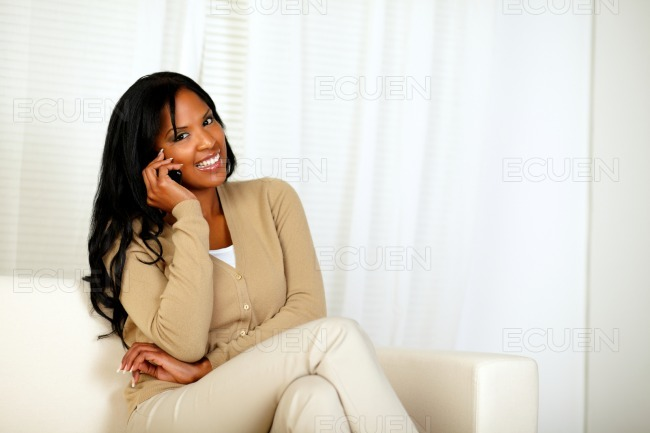 Black woman smiling at you while speaking on phone stock photo