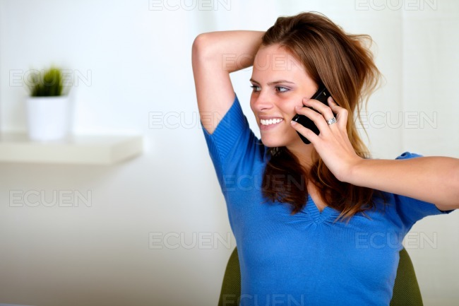 Blonde friendly young woman conversing on phone stock photo