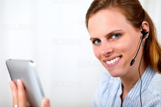 Blonde girl talking and holding tablet PC stock photo