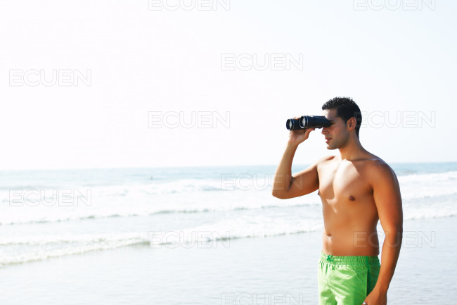 Boy with binoculars looking at the seashore stock photo