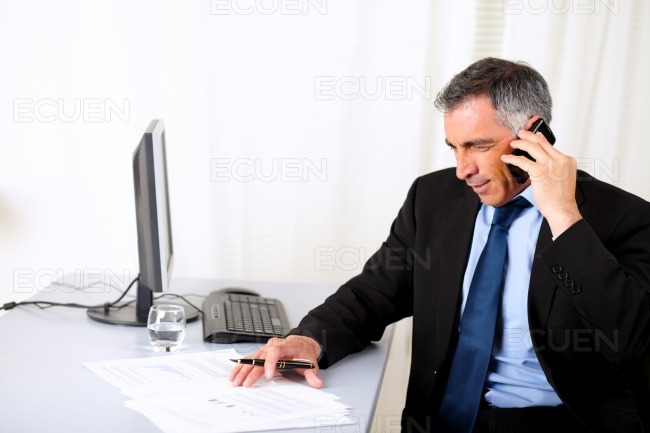 Businessman speaking on mobile at the office stock photo