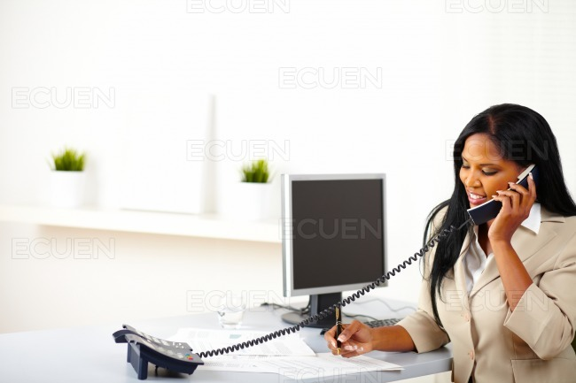 Businesswoman on phone while working stock photo