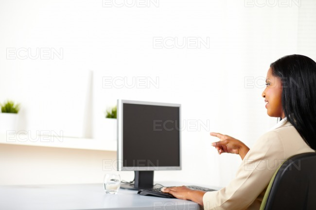 Businesswoman pointing to a monitor stock photo