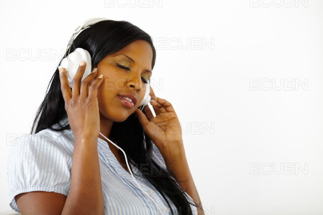 Calm young female listening to music stock photo