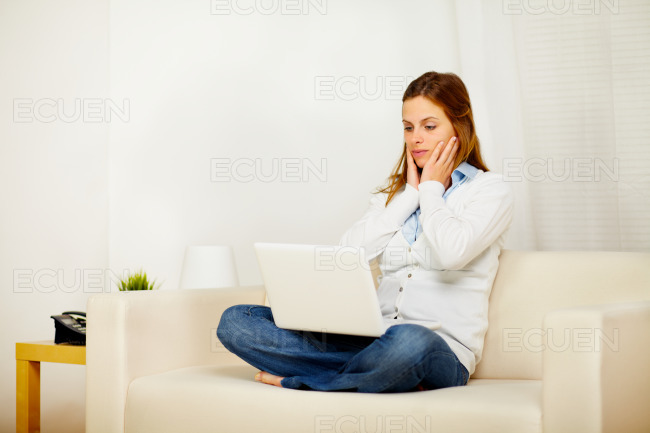 Casual girl working on sofa with a laptop stock photo
