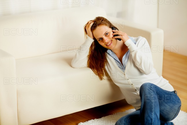 Casual woman on cell phone at home stock photo