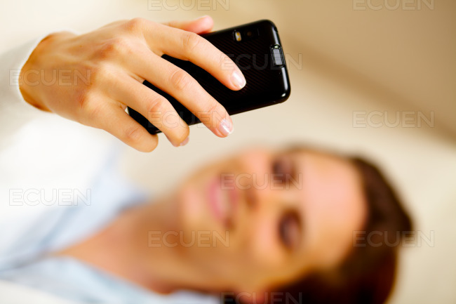 Caucasian woman using a cell phone at home stock photo