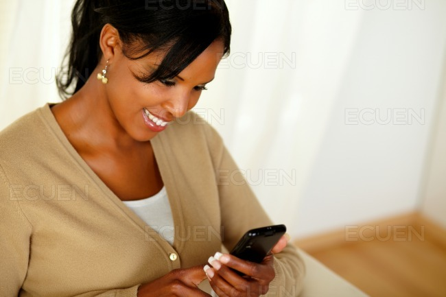 Charming adult girl reading a message on cellphone stock photo