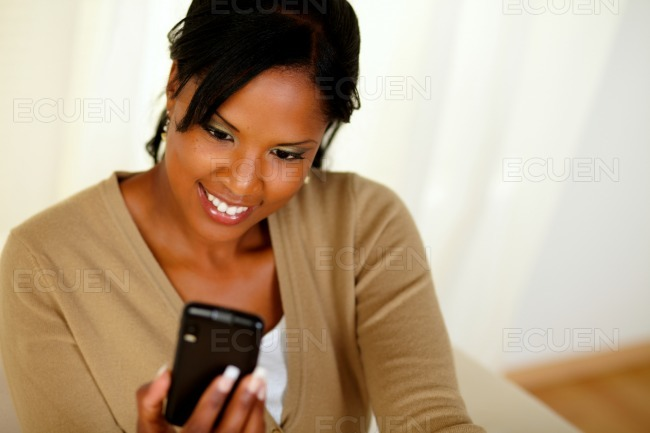 Charming black lady sending a message by cellphone stock photo