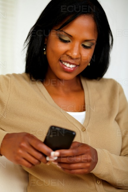 Charming black woman sending message by cellphone stock photo