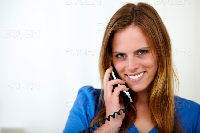 Charming blonde smiling young woman on phone stock photo