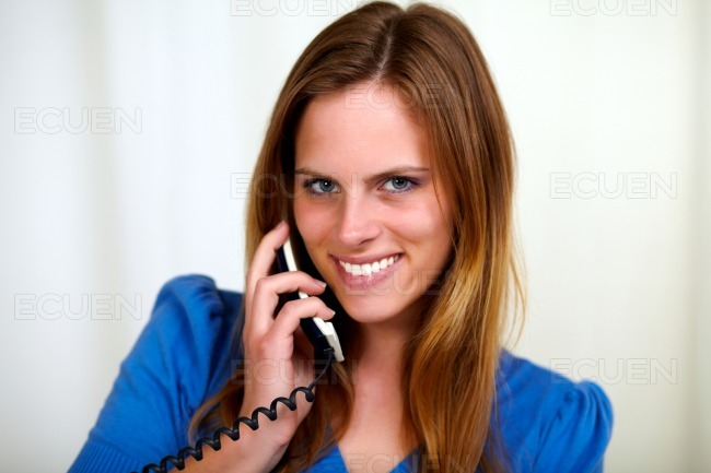 Charming blonde young woman talking on phone stock photo
