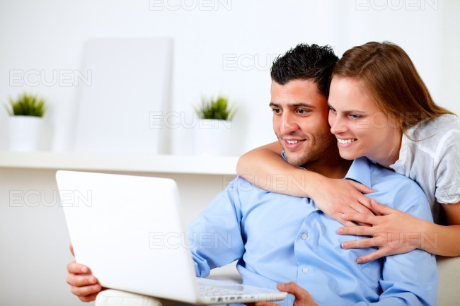 Charming couple using laptop together stock photo