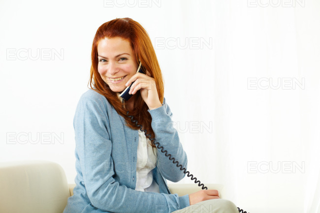 Charming lady smiling and using a phone stock photo