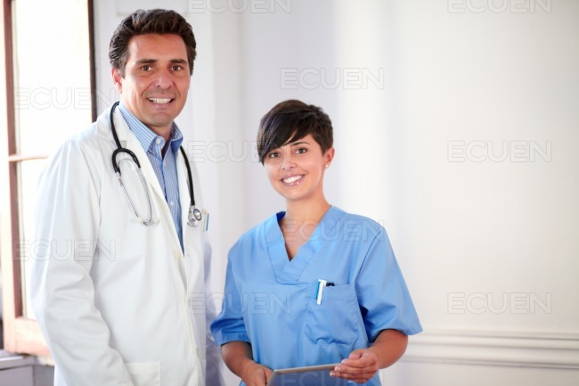Charming male doctor and pretty nurse standing stock photo