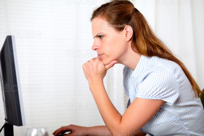 Charming pensive pretty girl looking on computer stock photo