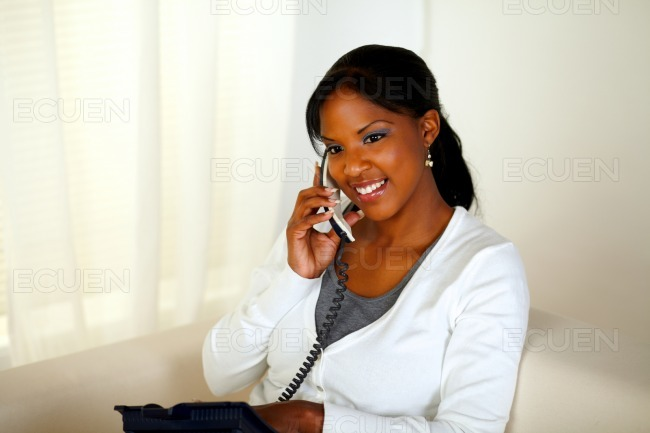 Charming relaxed young woman speaking on phone stock photo