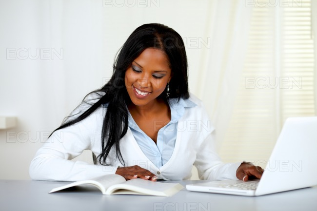 Charming student woman browsing a book stock photo